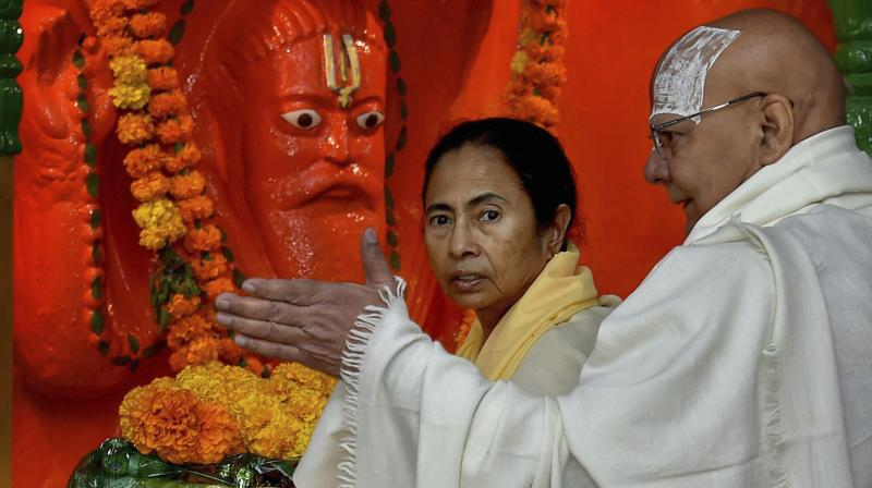 Chief minister Mamata Banerjee offers prayers at Kapil Muni Temple at Sagar Island, on Wednesday. Head priest Mohanta Gyandas is also seen in the photo. (Photo: PTI)