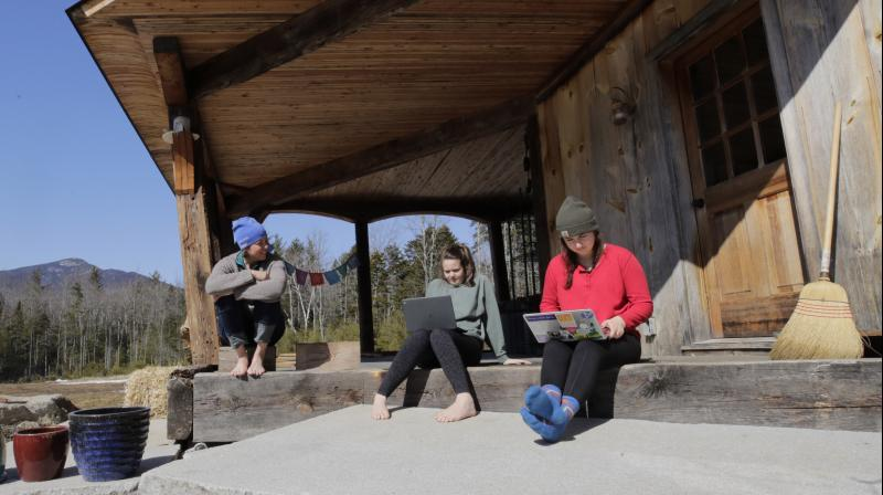 Ashley Bullard, left, sits on the porch of her family's rural home in North Sandwich, New Hampshire, as her daughters Raven, center, a senior in high school, and Willow, right, a freshman at Brandeis University, try to complete their classwork from home during the virus outbreak on a very limited internet connection, Thursday, March 26, 2020. In the town of 1,200, broadband is scarce. (Photo | AP)