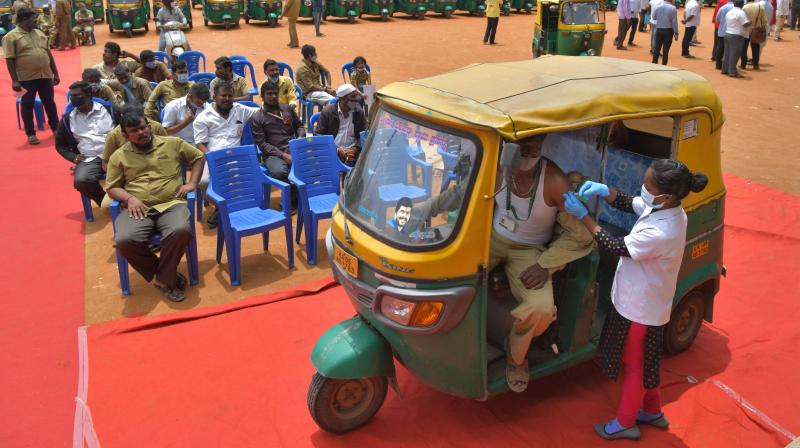 An auto rickshaw driver receives a jab of CoviShield vaccine against the Covid-19 coronavirus during a free vaccination drive for the drivers in Bangalore. (Photo: AFP)