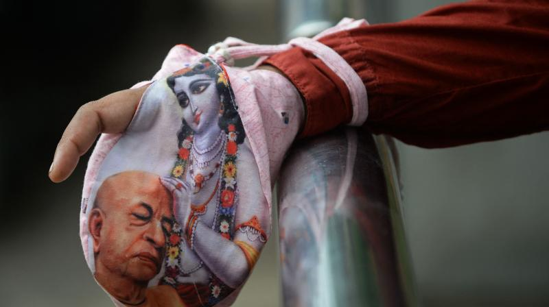 A devotee holds a bag containing prayer beads on the occasion of 'Janmashtami' festival marking the birth of Hindu god Krishna outside a temple closed due to the Covid-19 coronavirus pandemic in Mumbai. (Photo: AFP)