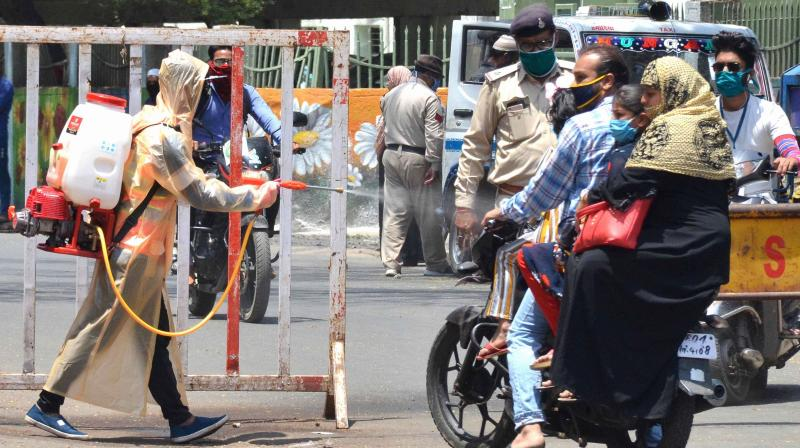 A BMC employee disinfectant on a bike in Bhopal. PTI photo