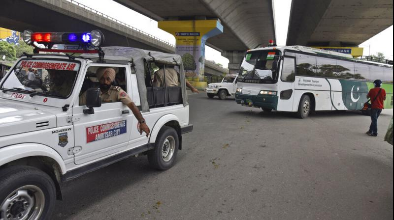 Punjab Police escort a Pakistan Tourism Development Corporation bus as it returns to Lahore without passengers, in Amritsar, India, on Saturday, August 10. (Photo: AP)