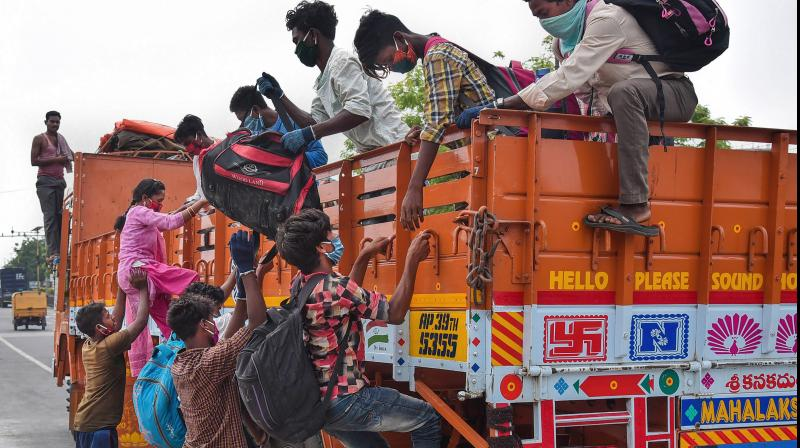 Migrants climb onto a truck to reach to their native place in Bihar, during the ongoing COVID-19 nationwide lockdown, in Vijayawada. PTI Photo