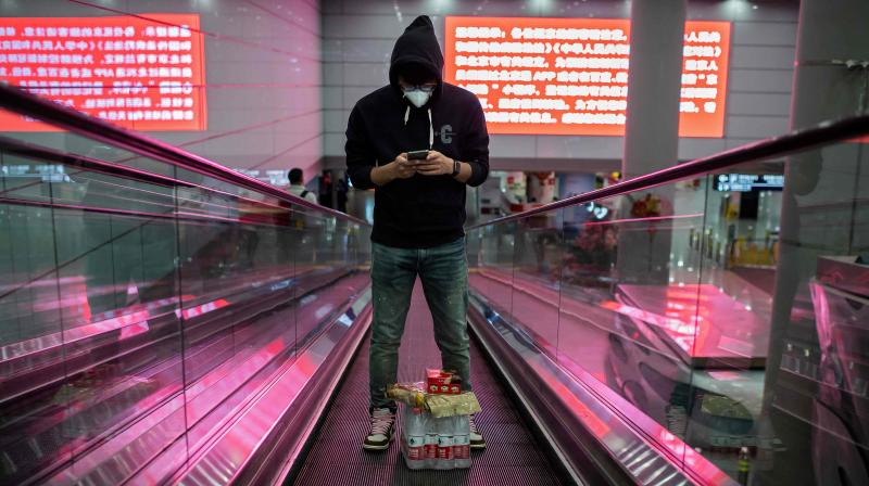 A man wearing a facemask and plastic gloves amid the concerns over the COVID-19 coronavirus uses an escalator at Beijing Capital International Airport. AFP photo