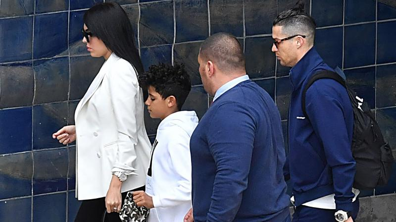 Juventus star Cristiano Ronaldo, his partner Georgina Rodriguez and son Cristiano Jr arrive at Madeira airport in Funchal, Portugal, on Monday. AFP Photo