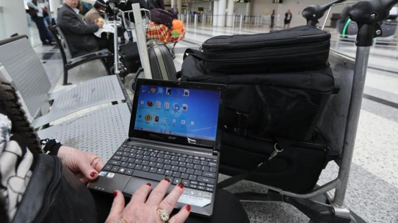 A woman checks her laptop at the Beirut international airport. The US and the UK have banned laptops and other devices on flights from some countries. (Photo: AFP)
