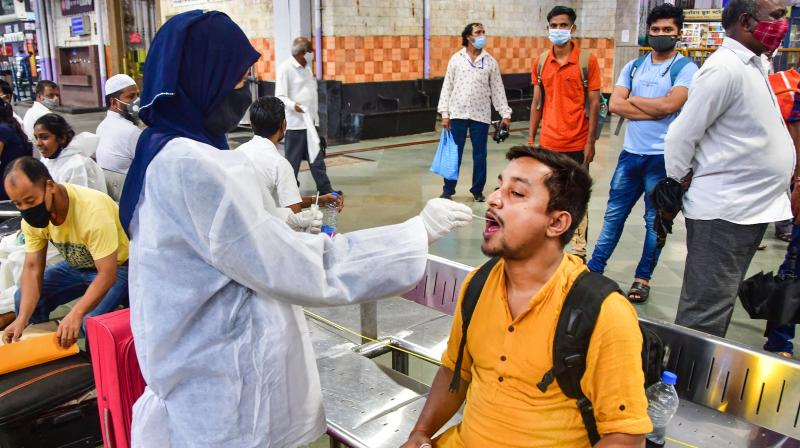 A BMC health worker collects swab sample of a passenger for COVID-19 test, at the CSMT station in Mumbai, July 19, 2021. (PTI)