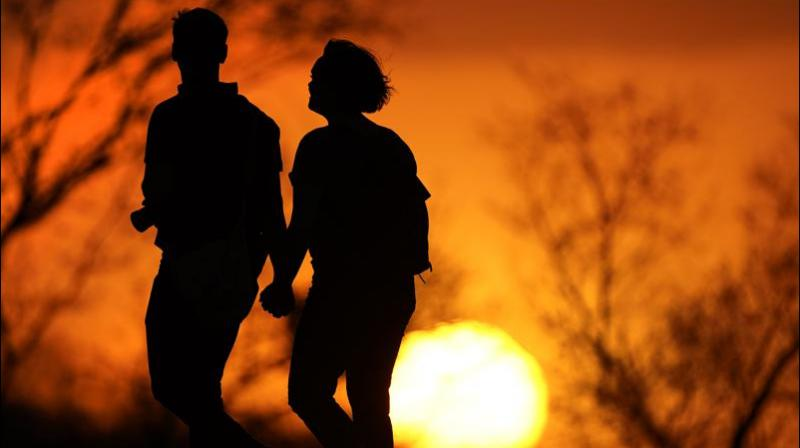 In this Wednesday, March 10, 2021 file photo, a couple walks through a park at sunset in Kansas City, Mo. According to a report released by the Centers for Disease Control and Prevention on Tuesday, July 20, 2021, U.S. life expectancy fell by a year and a half in 2020, the largest one-year decline since World War II.  (AP/Charlie Riedel, File)