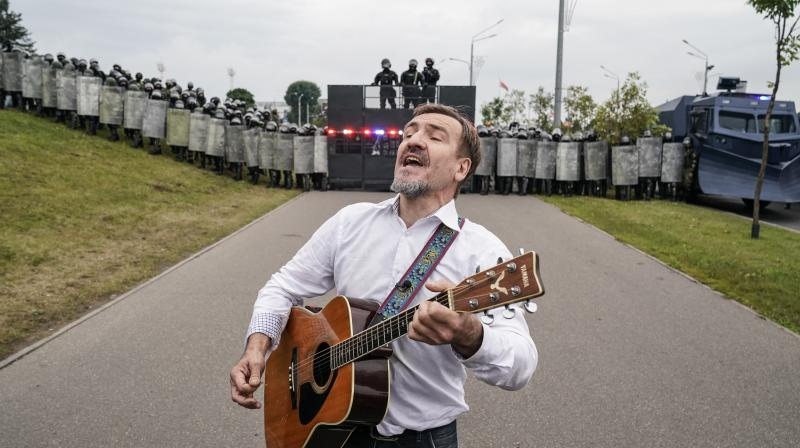 A man plays a guitar in front of riot police line during Belarusian opposition supporters rally near the Palace of Independence in Minsk, Belarus