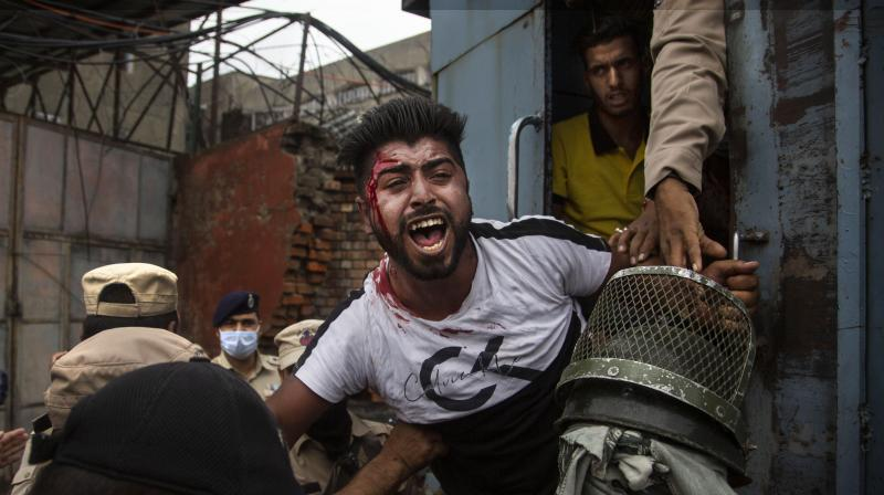 Policemen detain a Kashmiri Shiite Muslim as he attempts, along with others, to take out a religious procession in Srinagar