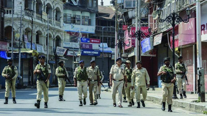 Security personnel patrol a deserted street in Srinagar on Friday. (Photo: PTI)