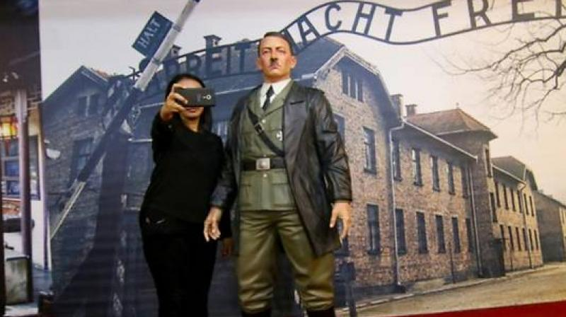 The exhibit features a sure-footed Hitler standing in front of a huge photo of the gates of Auschwitz. (Photo: AFP)
