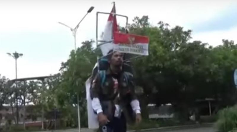He walks backwards with the help of a headpiece built with plastic pipes, fixed with a rear-view mirror which allows him to walk backwards. (Photo: Screengrab/Metro TV)