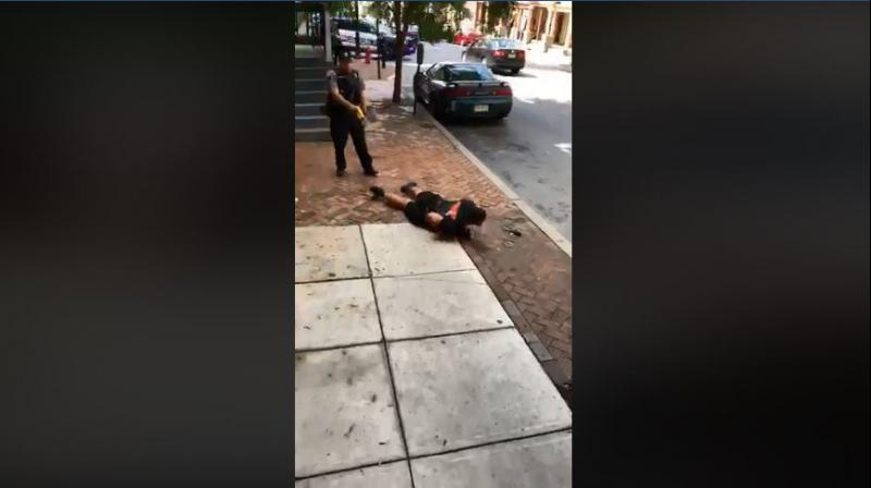 The video shows Williams sitting on a curb, being repeatedly asked to straighten his legs by Lancaster City Police Bureau Officer Philip Bernot. (Photo: Video Screengrab/Facebook)