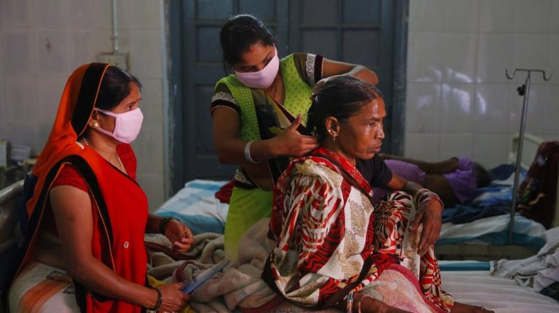 Relatives braid the hair of an Indian woman suffering from tuberculosis, admitted at the Lal Bahadur Shastri Government Hospital at Ram Nagar in Varanasi, India, Tuesday, March 13, 2018. Indian Prime Minister Narendra Modi on Tuesday launched a campaign to fast-track the India's response to tuberculosis, which is now the world's leading infectious killer. (Photo: AP)