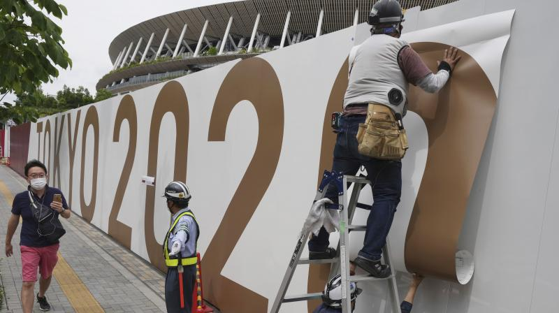 Workers paste the overlay on the wall of the National Stadium, where opening ceremony and many other events are scheduled for the postponed Tokyo 2020 Olympics, on June 2, 2021, in Tokyo.