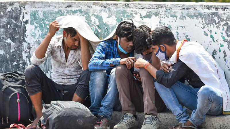 Migrants workers from Assam, Bihar and West Bengal wait at a roadside near Central Railway Station for arrangement to return to their native places, during ongoing COVID-19 lockdown, in Chennai. PTI Photo