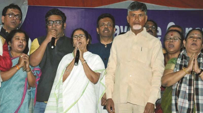 West Bengal chief minister Mamata Banerjee with TDP chief and Andhra Pradesh chief minister N Chandrababu Naidu stand for the national anthem after announcing the end of her 46-hour-long dharna in Kolkata on Tuesday. (Photo: PTI)