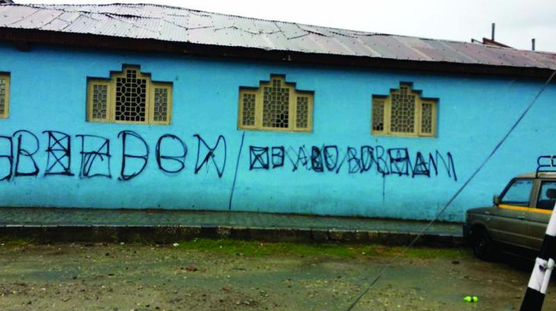 A graffiti on a wall reads 'Freedom....We are Burhan' in downtown Srinagar.