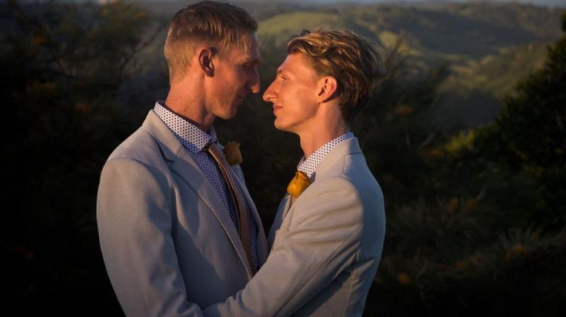 Australian Commonwealth Games sprinter Craig Burns (L) and fiance Luke Sullivan (R) embrace before their marriage ceremony at Summergrove Estate, New South Wales on January 8, 2018. (AFP Photo)