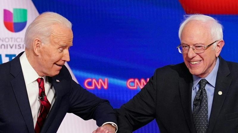 Joe Biden (left) and Bernie Sanders greet each other with a safe elbow bump before a Democratic Party presidential debate in Washington on March 15, 2020. Sanders has suspended his presidential campaign, clearing the way for rival Joe Biden to become the Democratic nominee to challenge Donald Trump in November. (AFP)