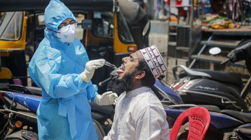 A medic takes samples for a coronavirus test in the containment zone of Kurla in Mumbai  on April 11, 2020. (PTI)