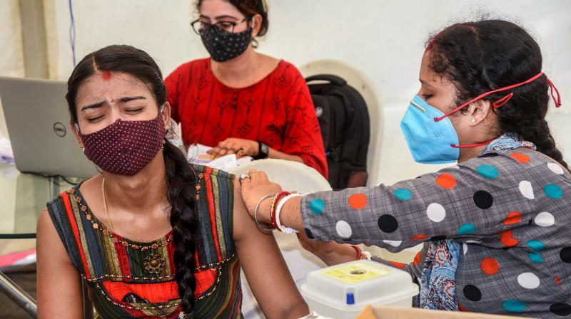 A beneficiary reacts as she receives a dose of COVID-19 vaccine. (PTI)