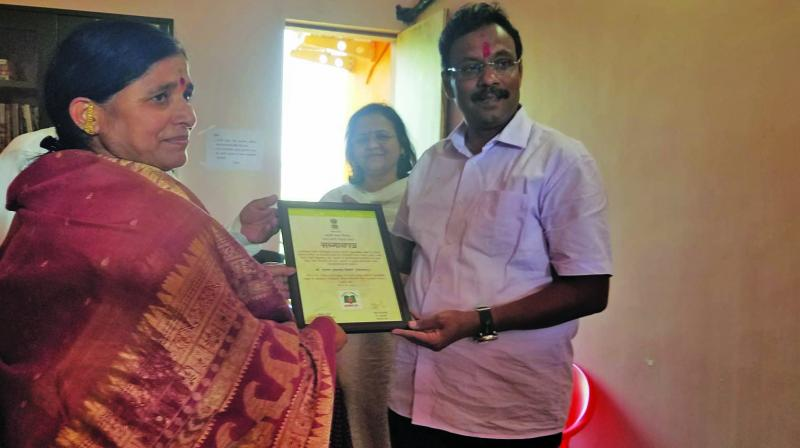 Minister Vinod Tawde felicitates a member of the Book Village project in Bhilar.