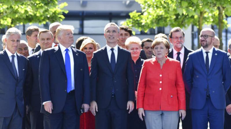 US President Donald Trump, left, NATO Secretary General Jens Stoltenberg and German Chancellor Angela Merkel walk through NATO headquarters at the NATO summit in Brussels. (Photo: AP)