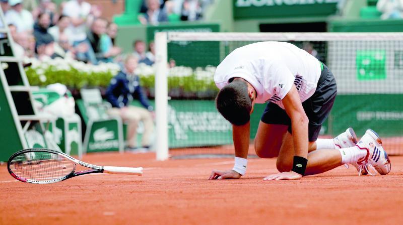 Serbia's Novak Djokovic falls while playing Austria's Dominic Thiem (above) in their French Open quarter-final in Paris on Wednesday. Thiem won 7-6 (7/5), 6-3, 6-0. (Photo: AP)