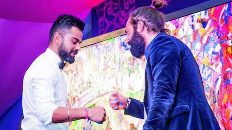 Virat Kohli with artist Sasha Jaffrey and latter's painting on him at the charity event.