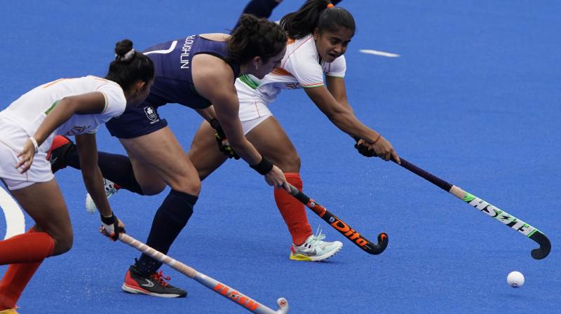 India midfield Neha Neha, right, and Ireland midfield Hannah McLoughlin (7) battle for the ball during a women's field hockey match at the 2020 Summer Olympics, Friday, July 30, 2021, in Tokyo, Japan. (AP/John Locher)
