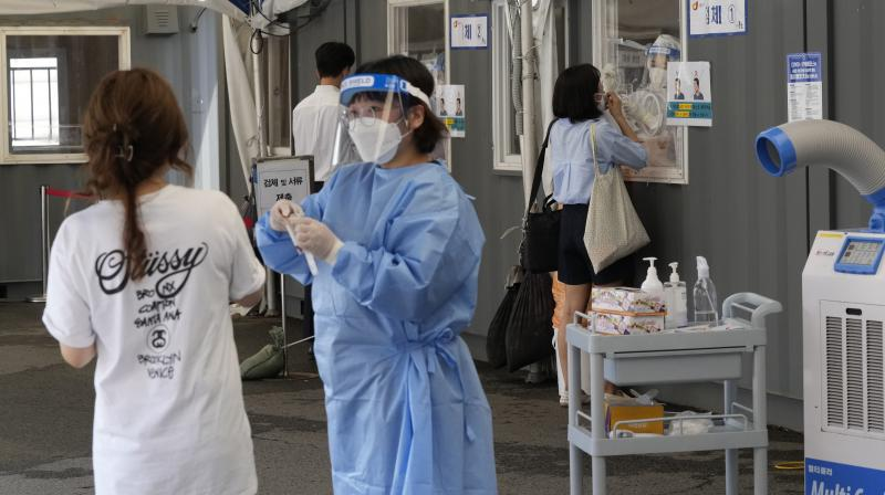 Medical workers takes nasal samples from residents for coronavirus tests at a makeshift testing site in Seoul, South Korea, Tuesday, July 20, 2021. (AP/Ahn Young-joon)