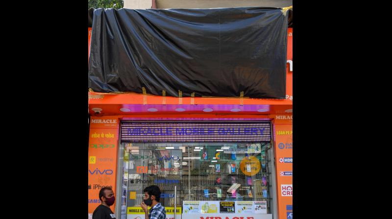 People stand outside a shop selling mobile phones from Chinese electronics company Xiaomi of which the front name is covered with a tarp, as calls for a boycott of Chinese goods gather pace following a border clash that killed 20 Indian soldiers, in Mumbai. PTI Photo