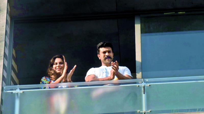 Ram charan Teja and his wife upasana Kamineni clap from the balcony of their house
