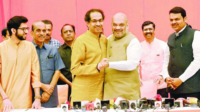Shiv Sena president Uddhav with BJP president Amit Shah greet each other at an event in Mumbai as Maharashtra chief minister Devendra Fadnavis and Aaditya Thackeray look on.