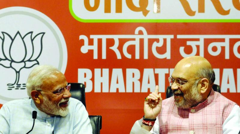 Prime Minister Narendra Modi with BJP president Amit Shah during a press conference at the party headquarters in New Delhi on Friday. (Photo: Pritam Bandyopadhyay)