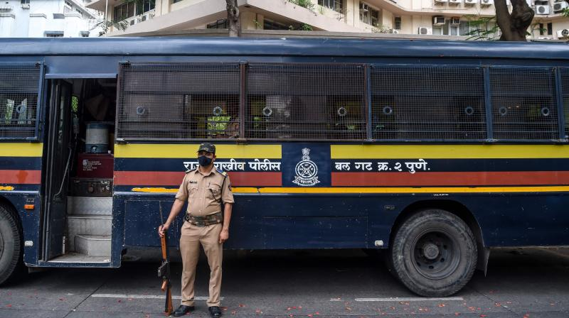 A police personnel belonging to the Maharashtra police force stands guard near a security bus. PTI photo