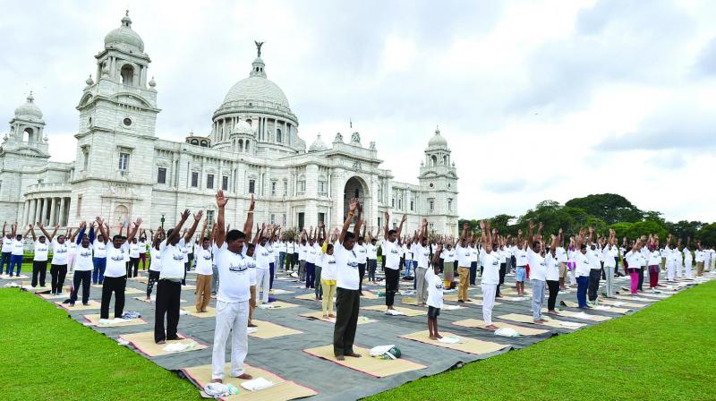 CISF personnel along with others perform yoga during the 5th International Day of Yoga in Kolkata on Friday. (Photo:  PTI)