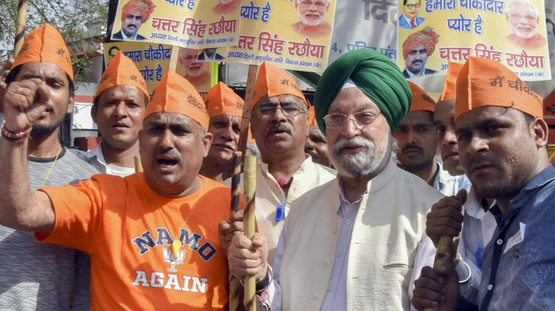 Hardeep Puri with party supporters outside Delhi BJP office on Wednesday. (Photo: PTI)