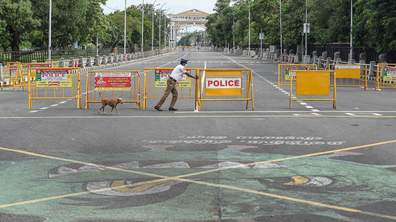 Traffic police personnel block a road during an intensified lockdown imposed as a preventive measure against the spread of coronavirus disease, in Chennai, Sunday. (PTI)