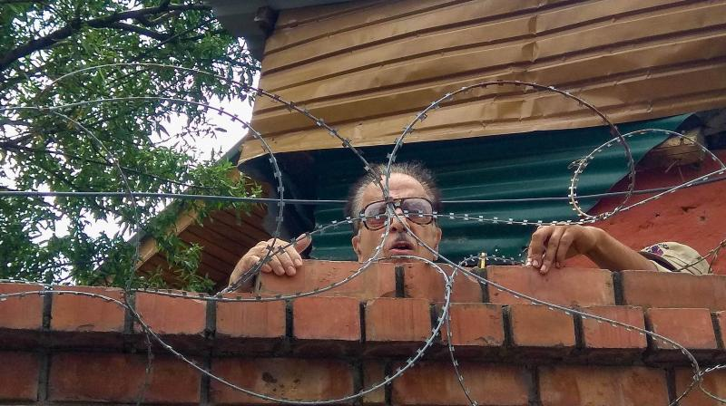Congress leader and former Union minister Saifuddin Soz climbs up the wall of his house to speak to a media person, in Srinagar, Thursday. (PTI)