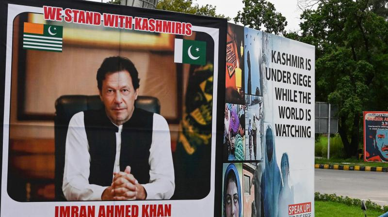 A motorcyclist rides past a billboard displaying a picture of Pakistan's Prime Minister Imran Khan along a street in Islamabad on August 4, 2020. (AFP)
