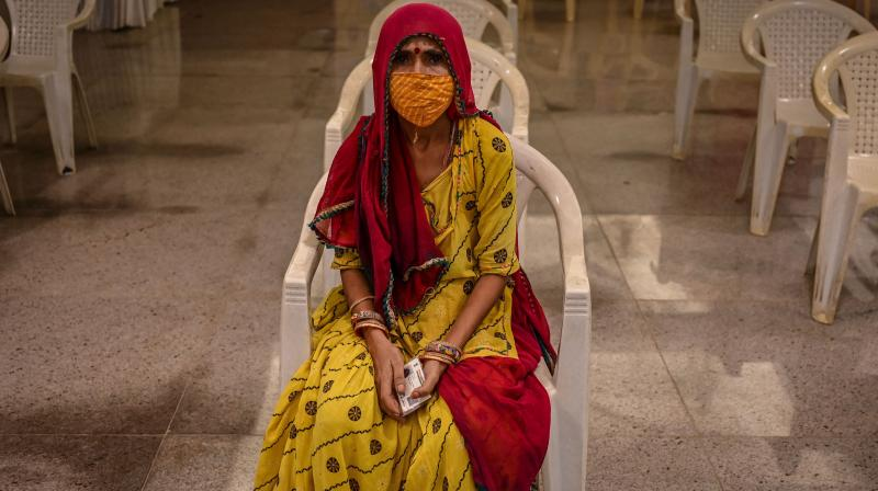 A woman waits for her turn to get inoculated with a dose of the Covaxin vaccine against the Covid-19 coronavirus, at a temporary vaccination centre set up inside a school in Mumbai. (Photo: AFP)