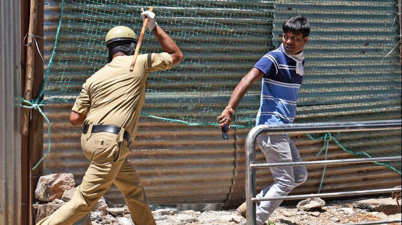 A policeman chases away a man from a coronanvirus hot-spot in Tippu Nagar on Mysore road in Bengaluru. (DC Photo: Satish B)