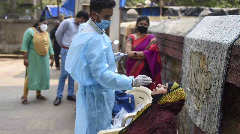 A health worker takes swab sample of a resident for COVID-19 testing in a housing society, amid a surge in coronavirus cases, at Nehru Nagar in Mumbai, Thursday, Feb. 18, 2021. (PTI)