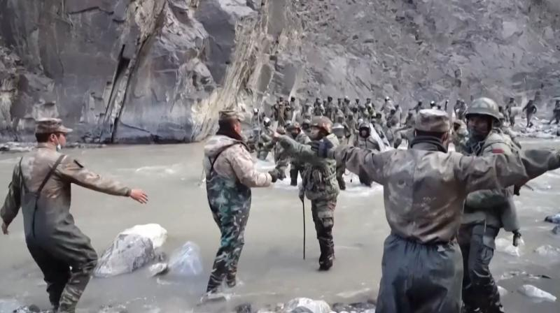 This video frame grab taken from footage recorded in mid-June 2020 and released by China Central Television (CCTV) on January 20, 2021 shows Chinese (foreground) and Indian soldiers (R, background) during an incident where troops from both countries clashed in the Line of Actual Control (LAC) in the Galwan Valley, in the Karakoram Mountains in the Himalayas. (Photo by - / CCTV / AFP)