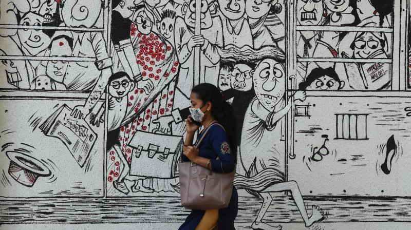 A woman walks past a mural depicting people travelling on a overcrowded public transport to raise awareness about maintaining social distancing and the use of masks, in Mumbai on March 2, 2021. (AFP)