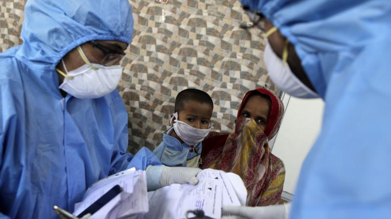 Doctors interact with people in a slum locality in Mumbai on April 6, 2020. As the coronavirus pandemic seems poised for a surge in India, medical authorities said they have decided to test everyone with flu-like symptoms in all hot spots of the outbreak. (AP)