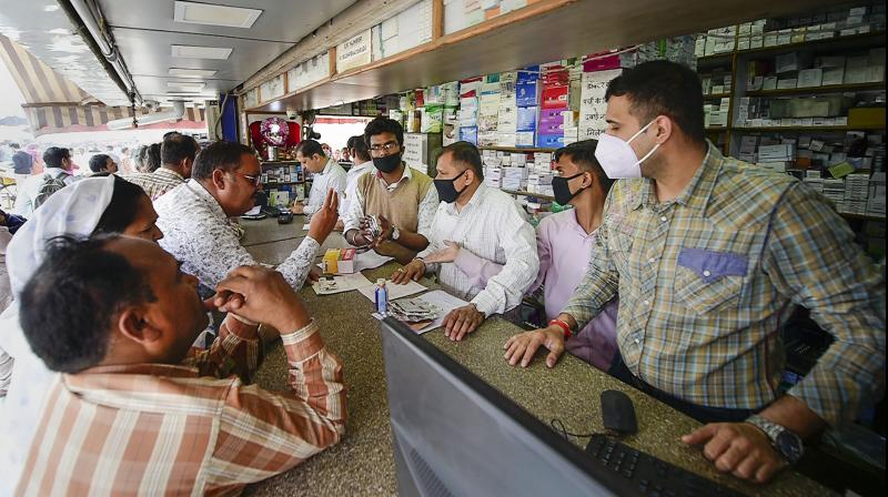 Salesmen at a chemist shop wear protective masks, in wake of the deadly novel coronavirus, outside Safdarjung Hospital, in New Delhi, Wednesday, March 4, 2020. (Photo | PTI)